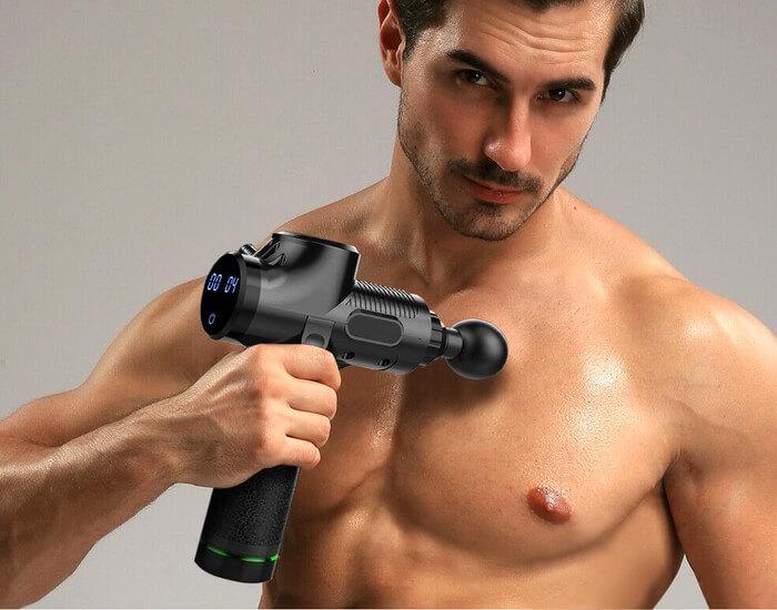 Homme utilisant un pistolet de massage